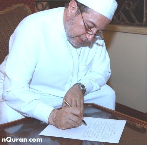 فضيلة الشيخ أيمن رشدي سويد وهو يكتب تزكيته لموقع ن للقرآن وعلومه